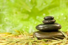 Piedras calientes del masaje del balneario en el ambiente verde Foto de archivo libre de regalías
