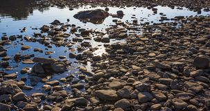 Piedras calientes en el agua azul del río de Dnister con resplandores imagen de archivo