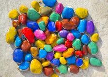 Piedras coloreadas que mienten en una superficie plana Imagen de archivo