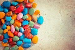Piedras coloreadas que mienten en una superficie plana Imagenes de archivo