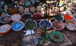 Piedras coloridas hermosas en buques de la arcilla con el tarazu indio para medir el peso imagenes de archivo