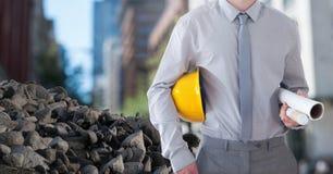 Piedras de los escombros con el trabajador de Construction del arquitecto que sostiene el casco y modelos en ciudad imagen de archivo libre de regalías