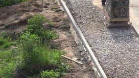 Piedras de los escombros de la presión del constructor en lugar del pavimento con el compresor de la placa 4K metrajes