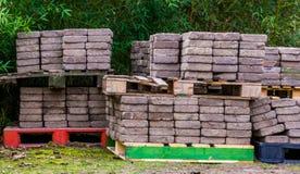 Piedras de pavimentación apiladas en las plataformas, materiales de construcción de la calle, industria del pavimento fotos de archivo