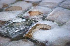 Piedras del adoquín cubiertas en hielo Foto de archivo