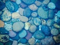 Piedras del adoquín debajo del agua azul Fotografía de archivo libre de regalías