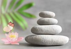 Piedras del balneario con el lirio de la flor en fondo ligero Fotografía de archivo libre de regalías