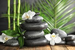 Piedras del balneario con las flores en la tabla de madera imagen de archivo