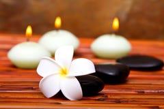 Piedras del balneario, velas y flor del frangipani Imagen de archivo