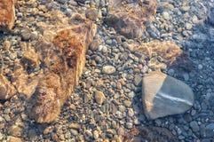 Piedras del guijarro del mar debajo del agua transparente en la parte inferior del mar Imagenes de archivo