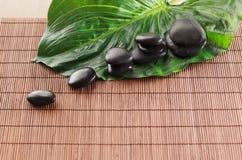 Piedras del masaje con las flores en la estera Imagen de archivo libre de regalías
