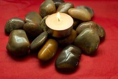 Piedras del río, guijarros y vela encendida Imagen de archivo libre de regalías