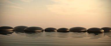 Piedras del zen en agua en salida del sol Foto de archivo