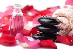 Piedras del zen, petróleo esencial y pétalos color de rosa aislados Imagen de archivo libre de regalías