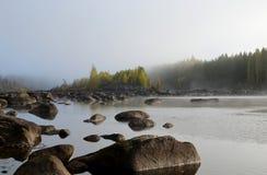 Piedras en agua en primero plano y una pequeña isla en niebla Imágenes de archivo libres de regalías
