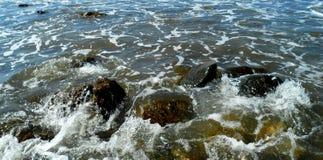 Piedras en espuma del mar Foto de archivo libre de regalías
