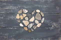 Piedras en forma de corazón de un guijarro en una madera vieja Foto de archivo libre de regalías