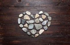 Piedras en forma de corazón de un guijarro en una madera vieja Fotos de archivo