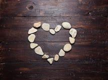 Piedras en forma de corazón de un guijarro en una madera vieja Fotos de archivo libres de regalías