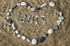Piedras en la arena en la forma del primer del corazón Imagen de archivo libre de regalías