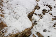 Piedras en la nieve a lo largo de una trayectoria con una pared de piedra que alinea el río Imagen de archivo
