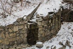 Piedras en la nieve a lo largo de una trayectoria con una pared de piedra que alinea el río Foto de archivo libre de regalías