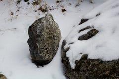Piedras en la nieve a lo largo de una trayectoria con una pared de piedra que alinea el río Imagenes de archivo