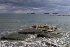 Piedras en la orilla y naves en el mar Fotografía de archivo