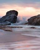 Piedras en la playa Chapoteo de ondas en el sol en el amanecer Fotografía de archivo