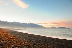 Piedras en la playa en la puesta del sol, Nueva Zelandia Foto de archivo libre de regalías