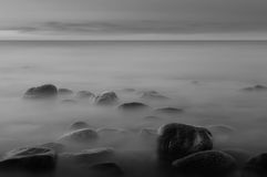 Piedras en un mar con exosure largo Foto de archivo libre de regalías