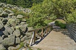 Piedras grandes del granito del río de piedra único en el río rocoso con el puente de madera en la montaña del parque nacional de Imagenes de archivo