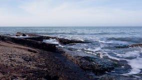 Piedras grandes en el mar en los rayos del sol de la mañana metrajes