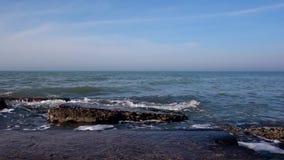 Piedras grandes en el mar en los rayos del sol de la mañana almacen de metraje de vídeo