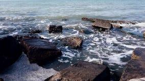 Piedras grandes en el mar en los rayos del sol de la mañana almacen de video