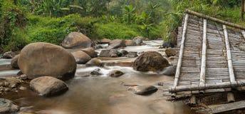 Piedras grandes y los restos del tejado en el río de la montaña Fotografía de archivo