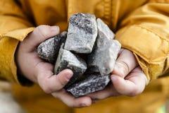 Piedras grises en pequeñas manos lindas del niño Imágenes de archivo libres de regalías
