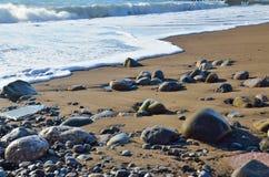 Piedras mojadas que mienten en la costa en la arena Onda del mar que rueda a Imagen de archivo