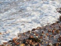 Piedras multicoloras, ondas con espuma Fotos de archivo
