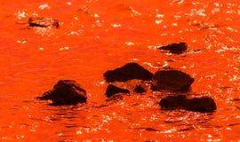 Piedras negras en agua anaranjada profunda Fotografía de archivo