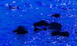 Piedras negras en agua azul profunda Imagen de archivo libre de regalías