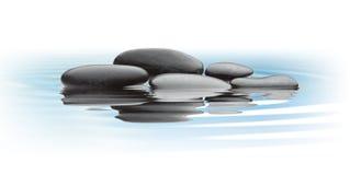 Piedras negras en el agua Foto de archivo