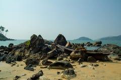 Piedras negras en una playa arenosa en el mar fotos de archivo