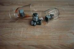 Piedras para el tulup de enfriamiento del whisky y de los glases en fondo de madera ligero Imagen de archivo