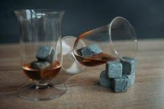 Piedras para el tulup de enfriamiento del whisky y de los glases en fondo de madera oscuro Imagenes de archivo