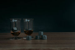 Piedras para el tulup de enfriamiento del whisky y de los glases en fondo de madera oscuro Fotos de archivo libres de regalías