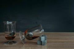 Piedras para el tulup de enfriamiento del whisky y de los glases en fondo de madera oscuro Imagen de archivo libre de regalías