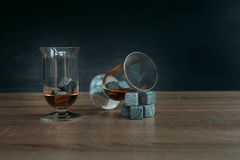 Piedras para el tulup de enfriamiento del whisky y de los glases en fondo de madera oscuro Imágenes de archivo libres de regalías