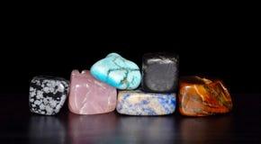 Piedras preciosas apiladas delante de fondo negro foto de archivo