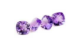 Piedras preciosas púrpuras naturales de la amatista aisladas en blanco Imagenes de archivo